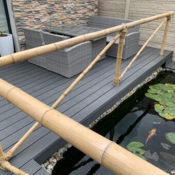 Hek om vijver van bamboepalen